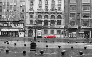Red car racing down boulevard