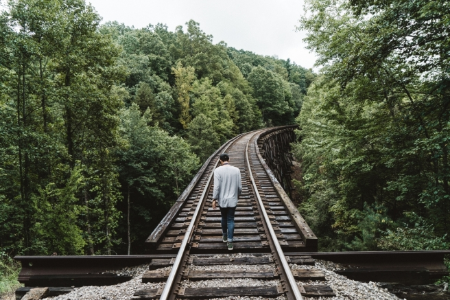 Man walking train tracks wilderness