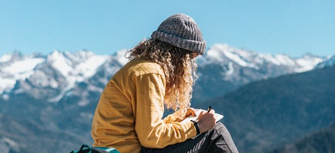 Freelance writer - woman with a backpack writing on a mountain peak