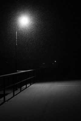 solitary stree lamp glowing in the dark above deserted platform winter landscape