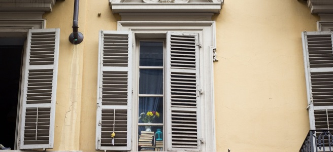 white window of old yellow house with books in the glass pane