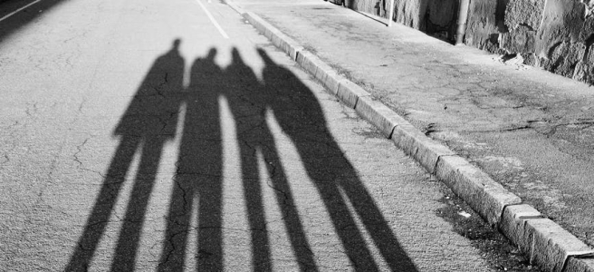frightening shadow of unrecognizable friends on shabby road